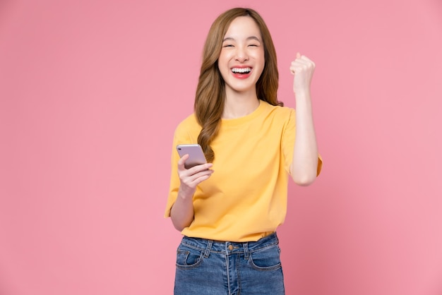 Cheerful beautiful asian woman holding smartphone with fists clenched celebrating victory expressing success on light pink background.