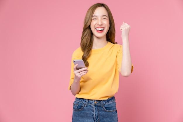 밝은 분홍색 배경에서 성공을 표현하는 승리를 축하하는 주먹을 꽉 쥐고 스마트폰을 들고 있는 쾌활한 아름다운 아시아 여성.