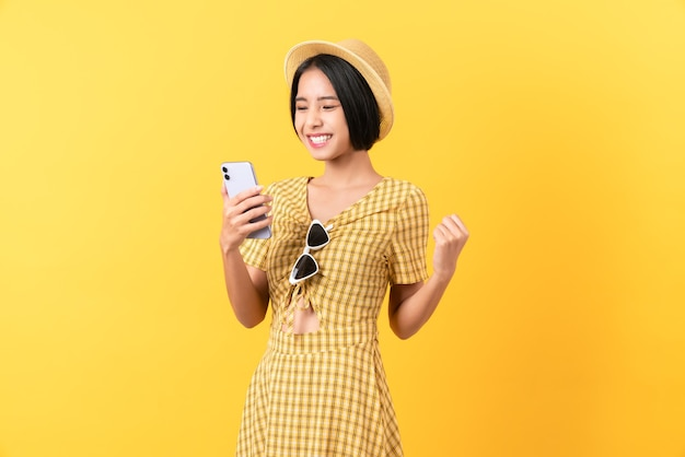 明るい黄色の背景で成功を表現する勝利を祝って握りこぶしでスマートフォンを保持している陽気な美しいアジアの女性