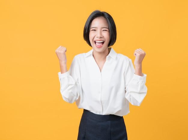 흰 셔츠를 입은 쾌활한 아름다운 아시아 여성은 팔과 주먹을 들고 강한 힘을 보여주며 승리를 축하하는 성공을 축하합니다.