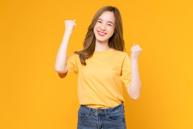 노란색 티셔츠를 입은 쾌활한 아름다운 아시아 여성은 팔과 주먹을 꽉 쥐고 강한 힘을 보여주며 승리를 축하하는 성공을 축하합니다.