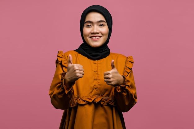 親指を立てて元気な美しいアジアの女性