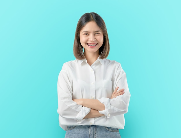 Cheerful beautiful asian woman stand and crossed arms on blue .