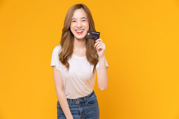 Cheerful beautiful asian woman in white t-shirt and holding mockup credit card on yellow background.