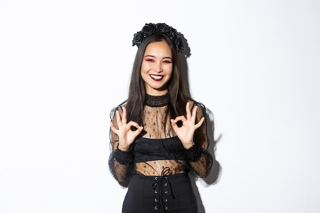Cheerful beautiful asian woman in witch dress showing okay gestures and smiling satisfied, approve halloween costume or advertisement, standing over white background.