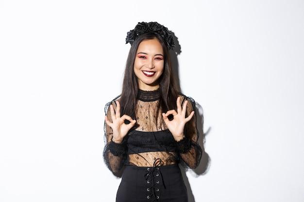 Bella donna asiatica allegra in vestito dalla strega che mostra i gesti giusti e sorridere soddisfatto, approva il costume o la pubblicità di halloween, stando sopra il fondo bianco.