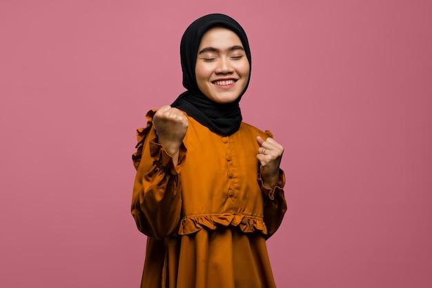 勝者の表情を持つ陽気な美しいアジアの女性