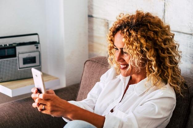 쾌활한 아름다운 금발 곱슬 성인 사람들이 여자는 미소하고 매력적인 여성과 화상 회의 및 채팅 개념-현대 전화로 셀카 사진을 찍는 가정 레저 활동을 즐길 수