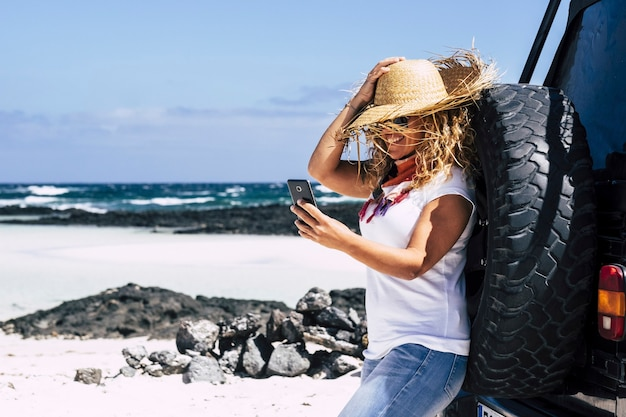 陽気な美しい金髪の観光客の女性が楽しんで、ビーチで携帯電話で笑顔
