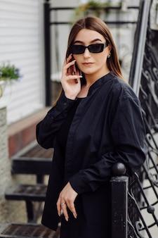 좋은 분위기에서 쾌활 한 아름 다운 갈색 머리 여자 외부 전화 사용