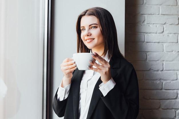 手にコーヒーのカップを持つ陽気な美しい実業家!