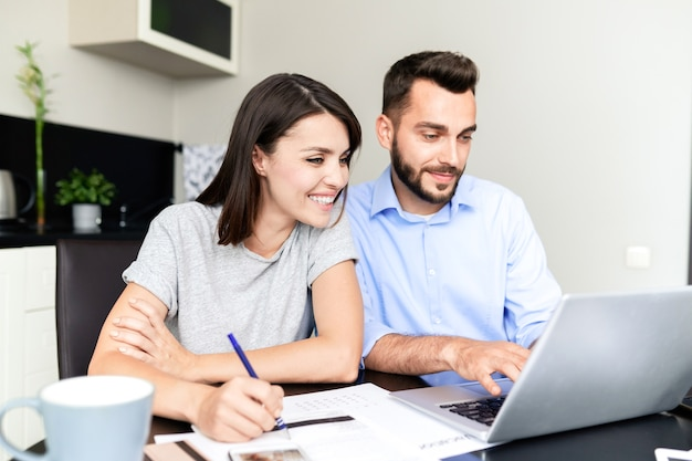 Cheerful beautiful couple sitting at table and using laptop while filling tax return form on website