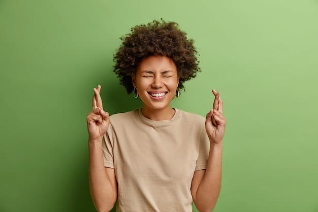 陽気な美しい巻き毛の民族の若い女性が指を交差させる結果の発表を待つ緑の壁に隔離されたカジュアルなtシャツに広く身を包んだ夢が叶うことを願って
