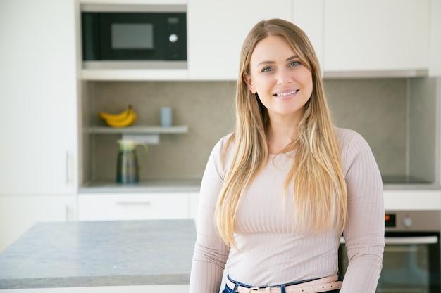 陽気な美しい金髪の若い女性がキッチンでポーズ