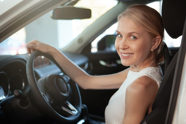 Cheerful beautiful female driver smiling to the camera from her car