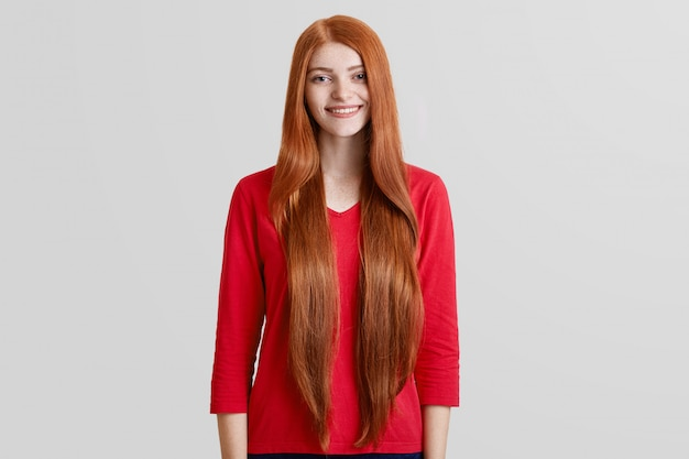 Cheerful beautiful female with very long red hair, freckled face, dressed in casual red sweater, poses against white wall, has pleasant gentle smile. positivity, beauty and style concept