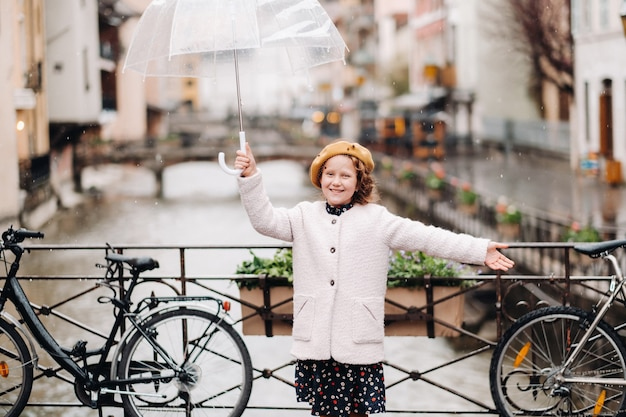 Cheerful beautiful girl in a coat with a transparent umbrella in annecy. france. the girl cheerfully raises an umbrella in the rain.