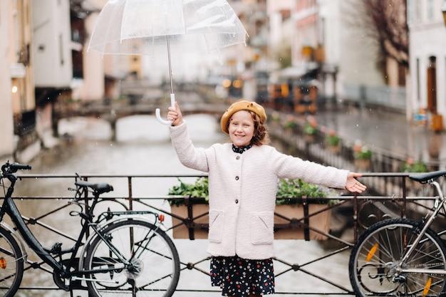 안시의 투명 우산 코트에 쾌활한 아름다운 소녀. 프랑스. 소녀는 빗속에서 유쾌하게 우산을 들어 올립니다.