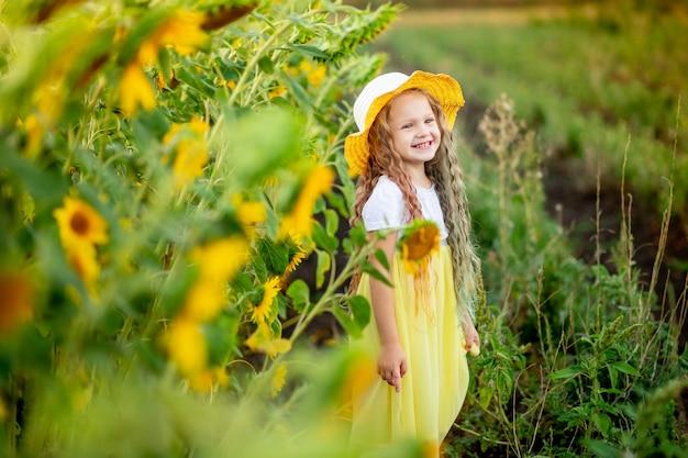 花と黄色のフィールドで麦わら帽子で陽気な美しい女の子