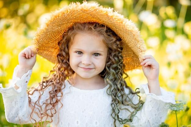 Веселая красивая девушка в соломенной шляпе летом в желтом поле с цветами.