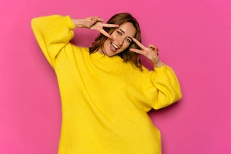 Cheerful beautiful girl in yellow sweater posing at camera showing peace sign