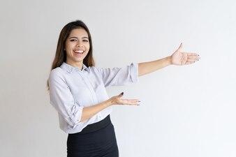 Cheerful beautiful girl presenting new product