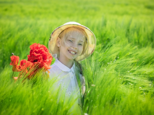 Cheerful beautiful girl with a bouquet of poppies in a field of green rye.