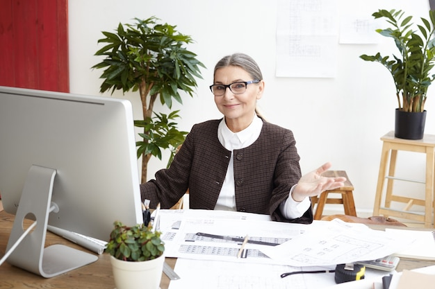 コンピューターの前に座って笑顔とジェスチャーで眼鏡をかけている陽気な美しい中年の白髪の女性建築家は、彼女が大きなプロジェクトに取り組み終えたときに幸せを感じています