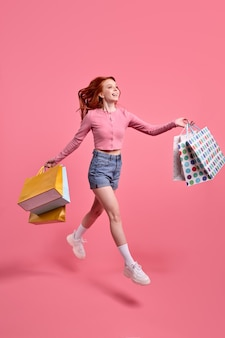 陽気な美しい赤毛の女性は、ピンクのシャツとデニムのショートパンツを着て、多くのパッケージ、孤立したピンクのパステルカラーの背景を身に着けているブラックフライデー中毒の買い物客を急いで高速でジャンプします