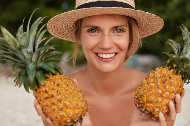Cheerful beautiful smiling woman with attractive look, broad smile, wears summer straw hat, holds two pineapples, going to make juice, enjoys good rest in tropical country. female tourist with fruits