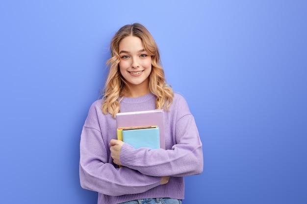 Веселая красивая девушка-подросток студент держит книги, изолированные на пастельно-синей стене студийный портрет