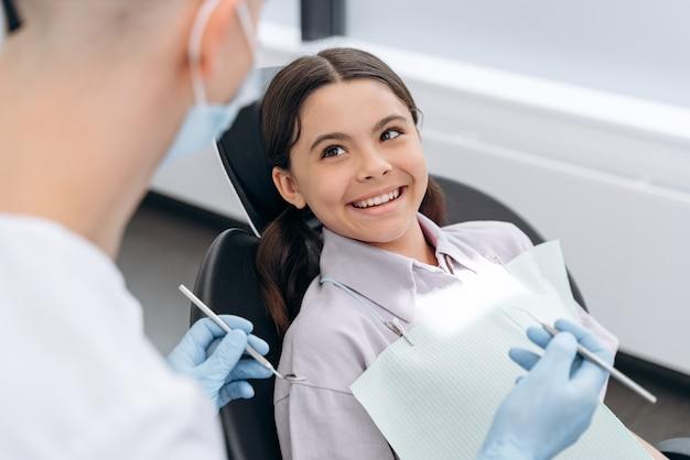 명랑하고 아름다운 십대 소녀는 치과 의사와 의사 소통합니다. 치과 도구를 들고 치과 의사