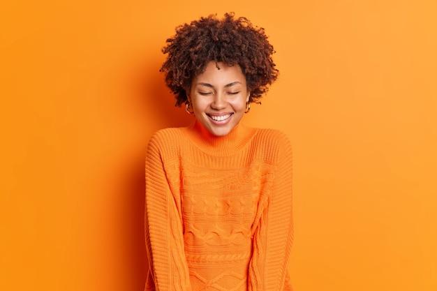 Веселая красивая женщина закрывает глаза и широко улыбается, носит свитер с длинными рукавами, позирует на фоне ярко-оранжевой стены, имеет счастливую улыбку на лице
