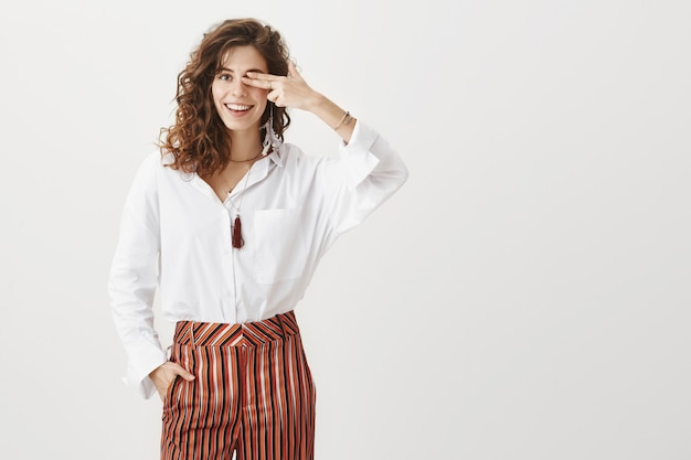 Cheerful beautiful woman covers one eye, smiling