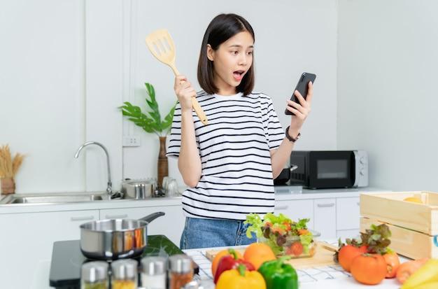 テーブルの上の鍋と様々な緑の葉野菜のスマートフォンとサラダボウルを持つ陽気な美しい女性の手。朝、台所で友人と携帯電話で話している