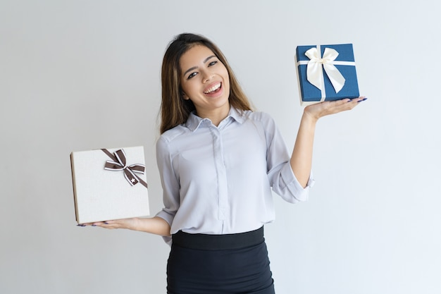 Cheerful beautiful woman holding two gift boxes