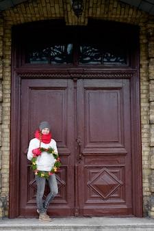 ドアの前にクリスマスリースを保持している赤い手袋と白いジャケットの陽気な美しい女性