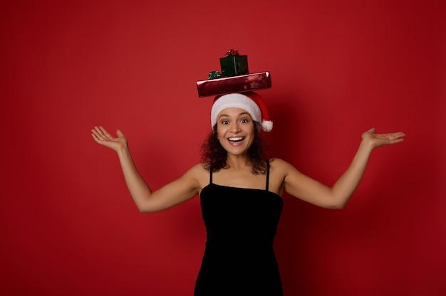 산타 모자와 이브닝 블랙 드레스를 입은 쾌활한 아름다운 여성은 상상의 카피 공간을 들고 머리에 크리스마스 선물을 얹은 카메라를 보며 미소를 짓고 손바닥을 들어올립니다. 빨간색 배경