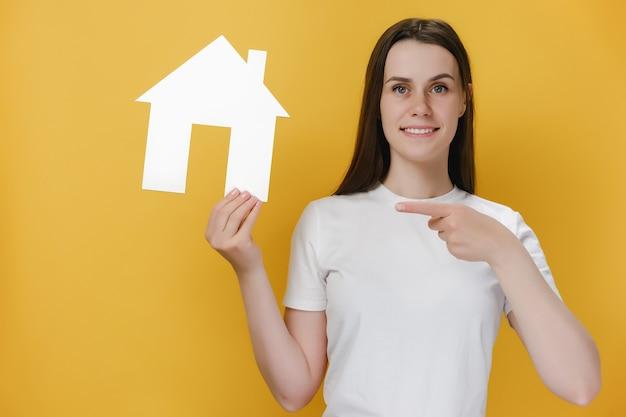 Веселая красивая женщина указывая на бумажный дом