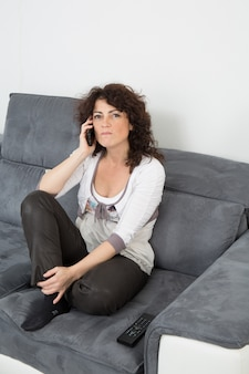 Cheerful beautiful woman sitting on the sofa