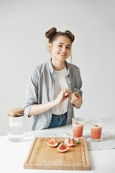 흰 벽에 로즈마리와 함께 자몽 해독 스무디를 장식 웃는 쾌활한 아름다운 여자. 건강한 영양.