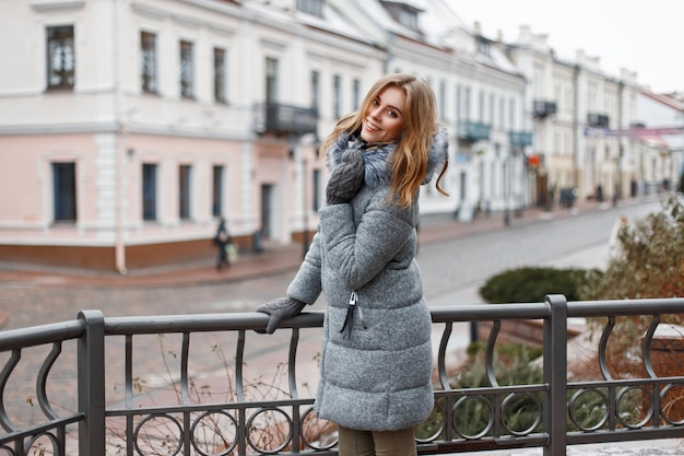 Cheerful beautiful woman in stylish winter clothes walking on a winter day in the city