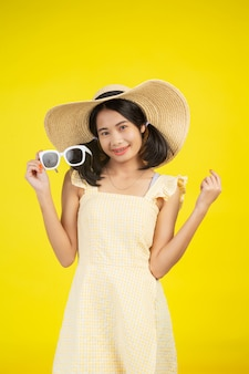 A cheerful beautiful woman wearing a big hat with white glasses on a yellow .