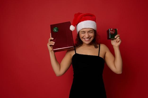 이브닝 드레스와 산타 모자에 아름 다운 이빨 미소와 쾌활 한 아름 다운 여자는 빨간색 배경에 포즈 크리스마스 선물을 들고 기뻐합니다. 광고 복사 공간이 있는 새해 복 많이 받으세요.