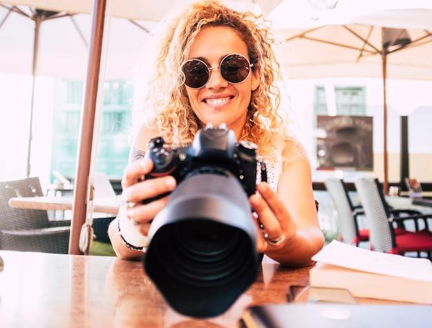 笑顔のバックディスプレイの写真を見て現代の大きなプロの反射カメラを持つ陽気な美しい女性