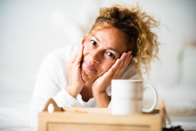 陽気な美しい若い大人の白人女性の肖像画は、お茶やコーヒーと一緒にベッドの寝室に横たわっています-自宅で幸せな人々は朝の目覚めの概念をお楽しみください