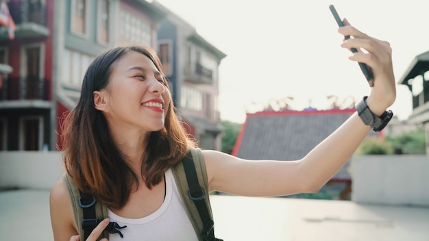 Cheerful beautiful young asian backpacker blogger woman using smartphone taking selfie