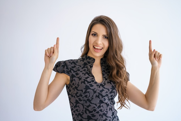 Cheerful beautiful young brunette girl with long hair in a dress poses on a white background, raises her fingers up