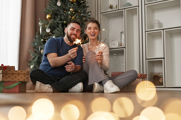 Cheerful beautiful young caucasian couple in cozy wear sitting against christmas tree and holding bu...