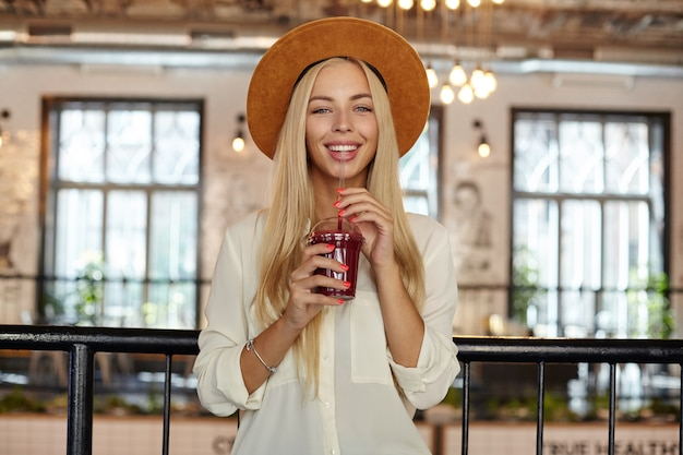 Bella giovane femmina allegra con capelli biondi lunghi che osserva felicemente mentre posa sopra l'interno del caffè, che tiene la tazza di limonata nelle mani